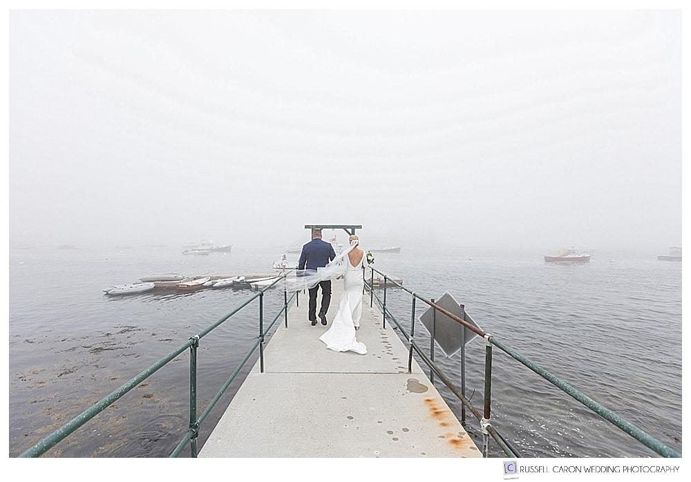 bride and groom walking towards a dock
