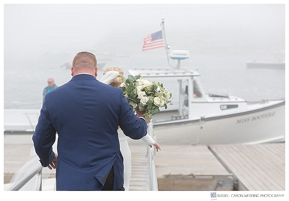 bride and groom walking towards a lobster boat