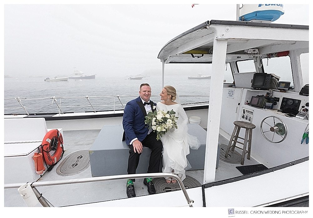 bride and groom sitting on a lobster boat in the fog