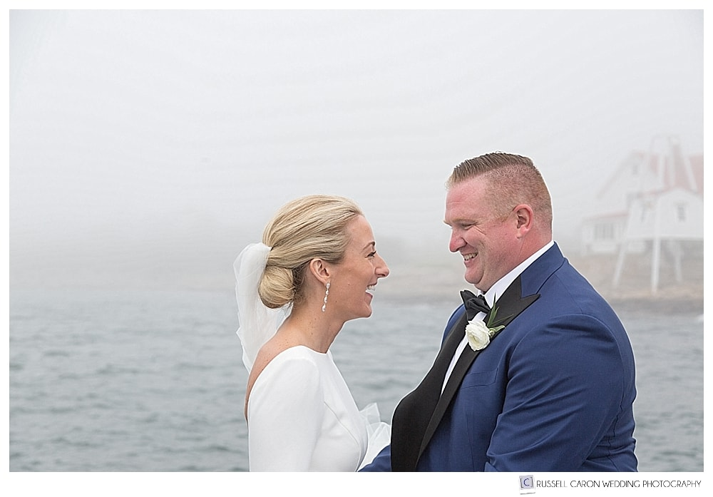 bride and groom in front of a lighthouse in the fog