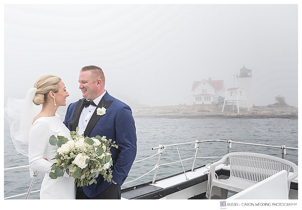 bride and groom on a lobster boat, on a foggy day, in front of the Hendricks Head Lighthouse on Southport Island, Maine