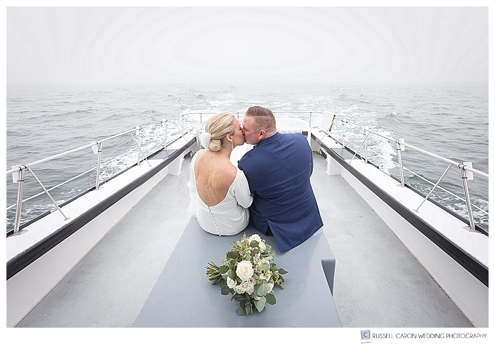 bride and groom kissing on a lobster boat, in the fog