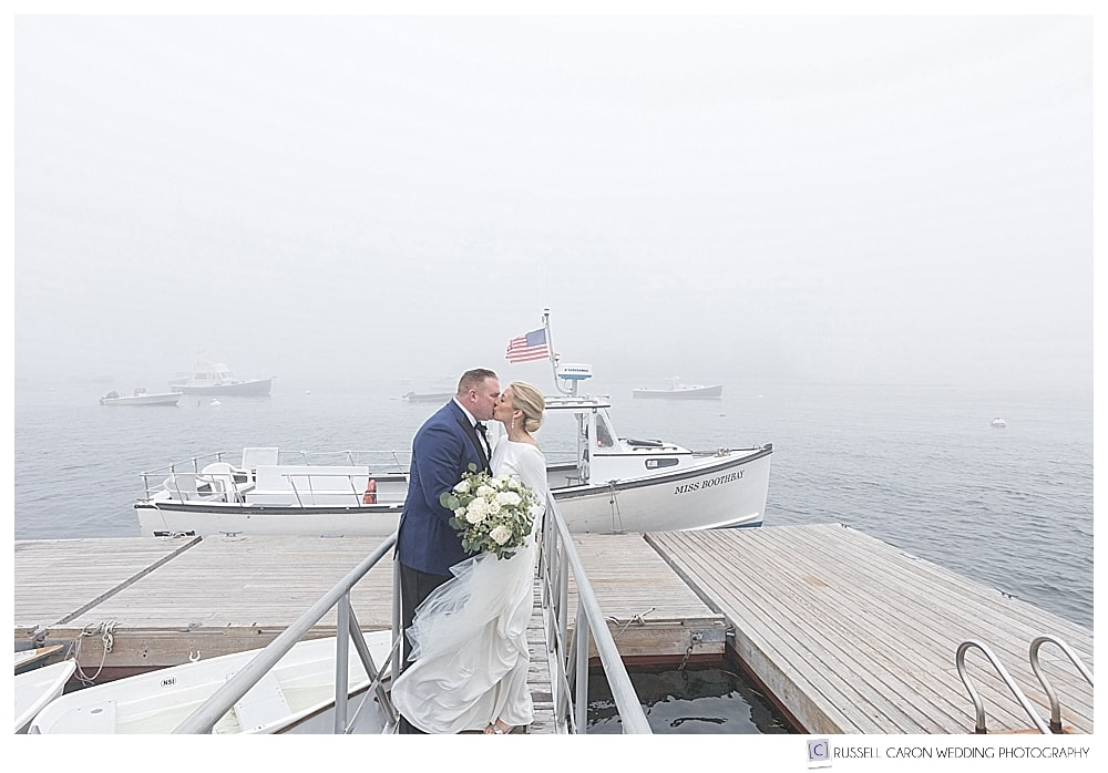 bride and groom kissing on a dock in front of a lobster boat