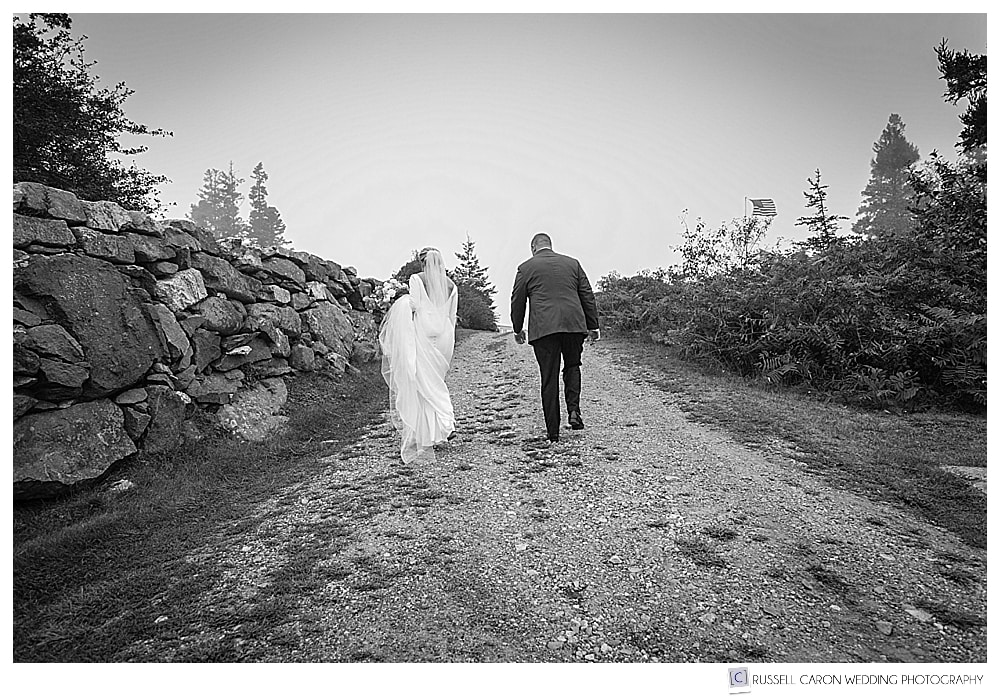 black and white photo of bride and groom walking up a hill