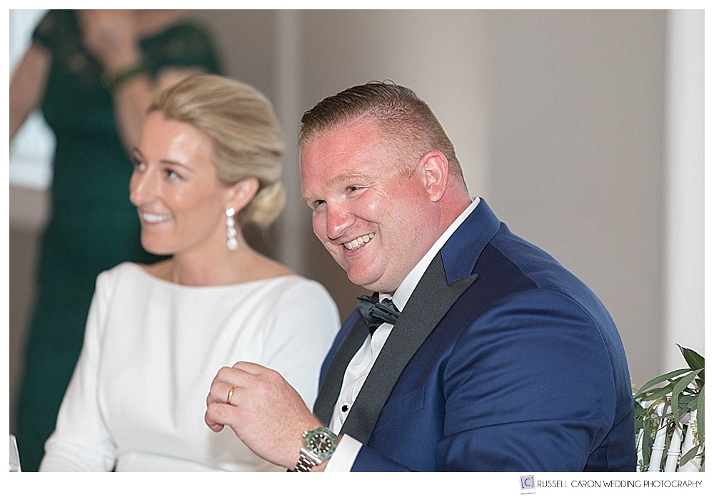 bride and groom sitting together at their wedding reception