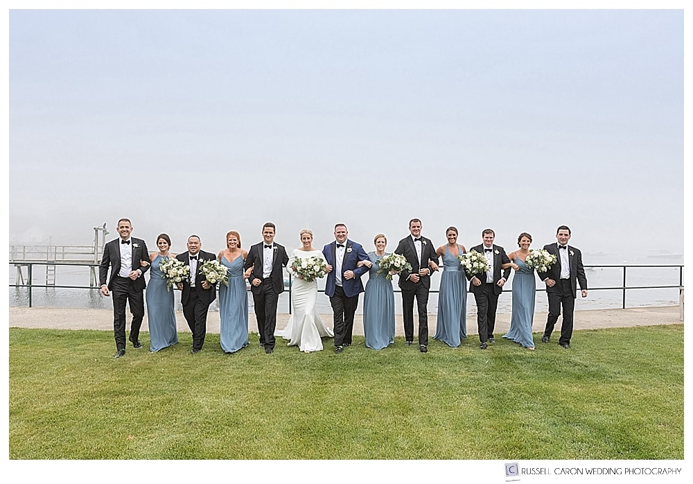 bridal party walking with arms linked together