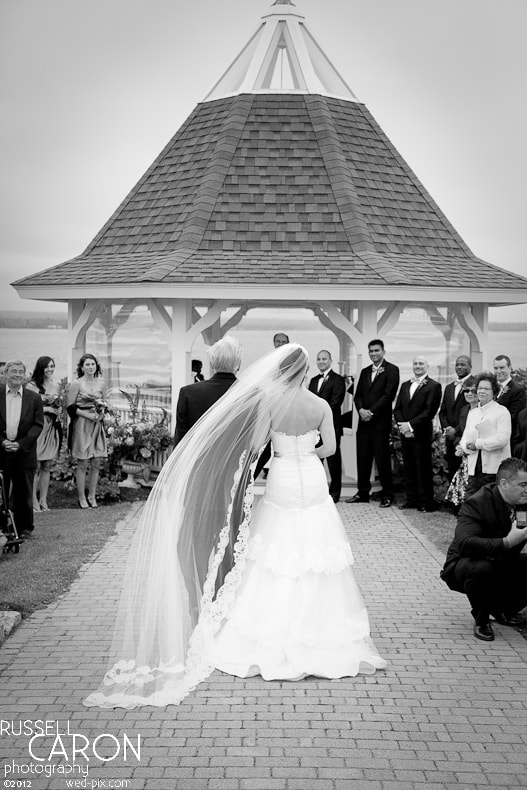 Bride's veil blows in the wind at a Maine wedding