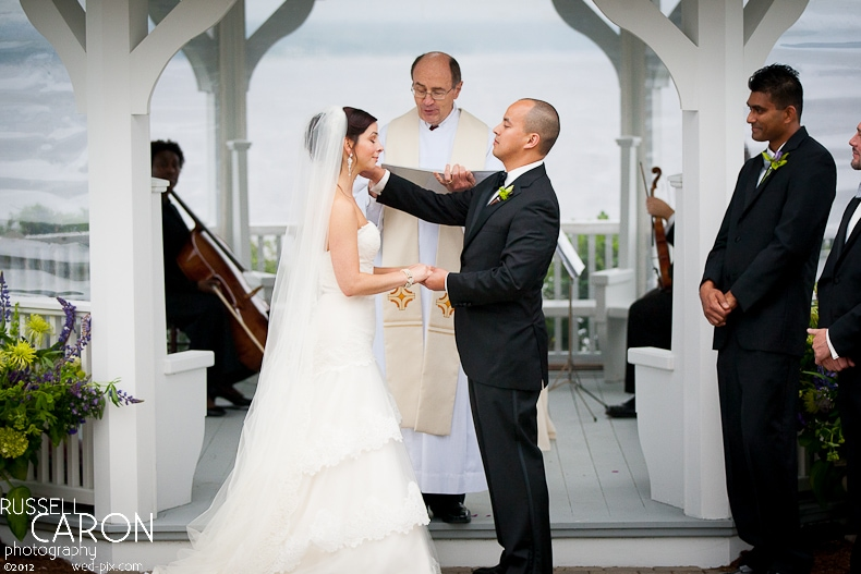 Grrom wipes away a tear from the bride's face