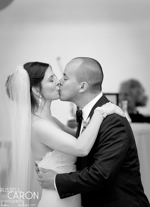 Bride and groom during wedding ceremony first kiss