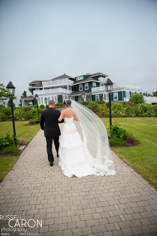 Bride and groom with veil blowing in the wind