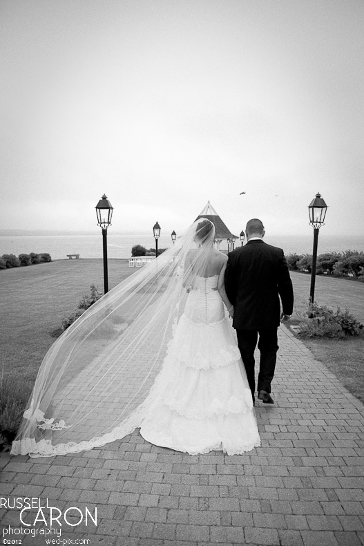 Bride and groom walking hand in hand with bride's veil blowing
