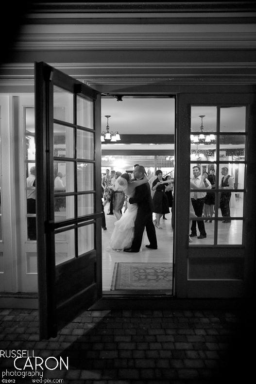Outside looking inside at bride and groom dancing