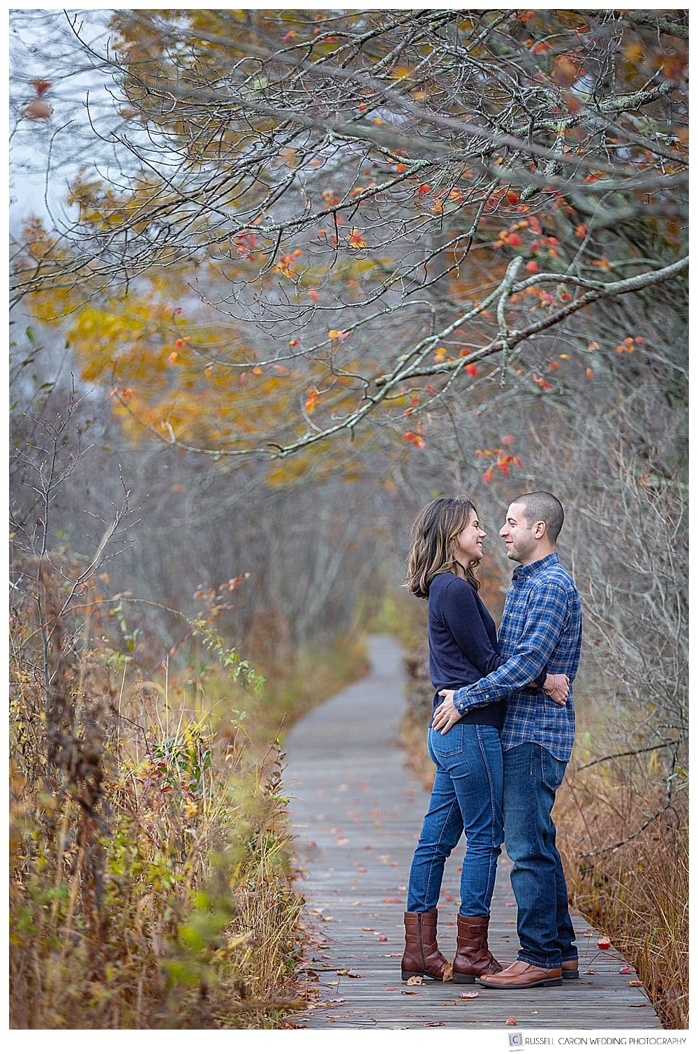 man and woman hugging each other on a wooden board walk in the fall foliage