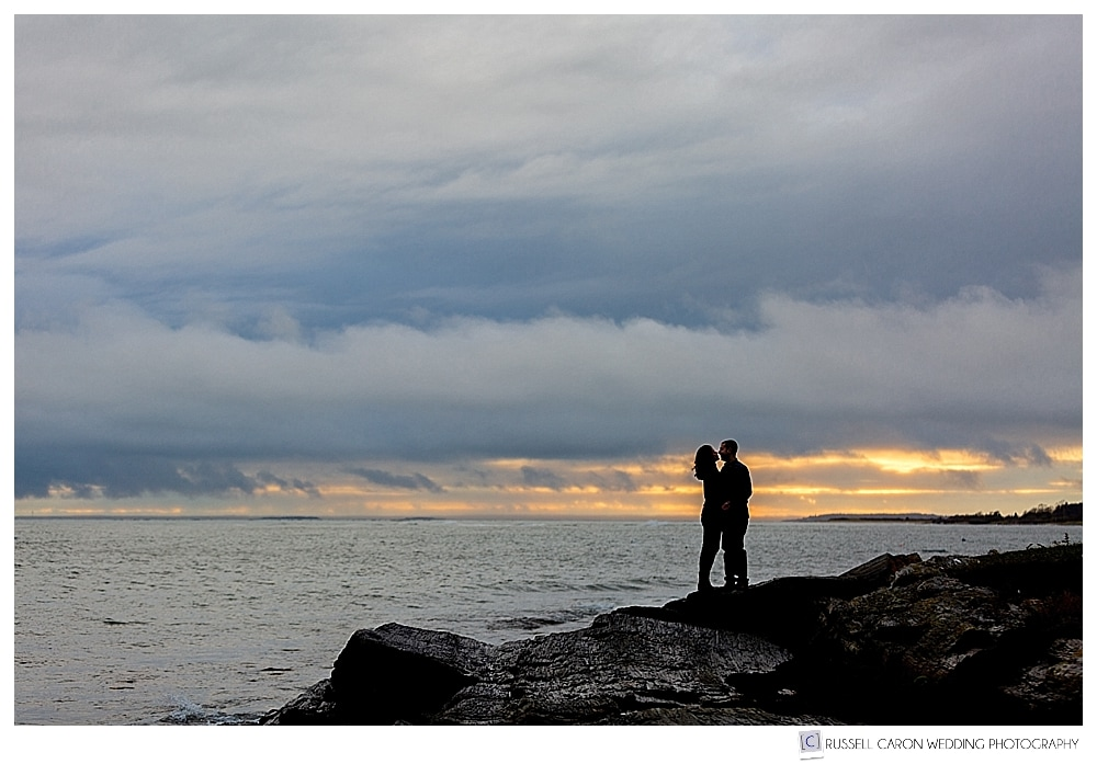 man and woman standing on the rocks, during their Kettle Cove, coastal Maine engagement session