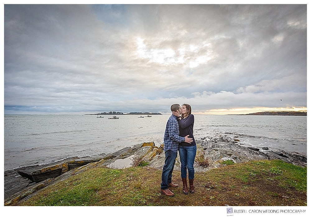 man and woman kissing in Kettle Cove, during their coastal Maine engagement photos