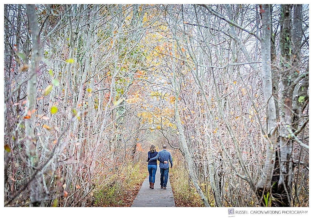 man and woman walking away on a boardwalk in the fall foliage, during their coastal Maine engagement session