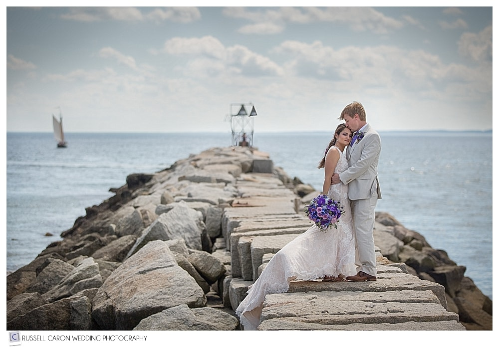 bride and groom on the kennebunkport breakwater