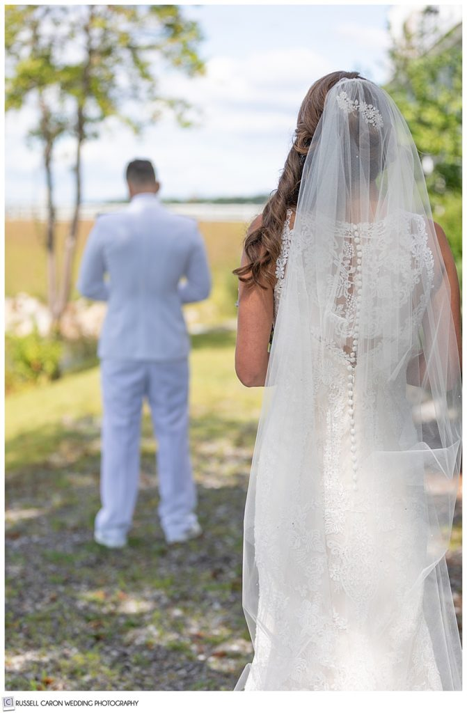 bride, with her back to the camera, and groom with his back to the bride, just before their wedding day first look