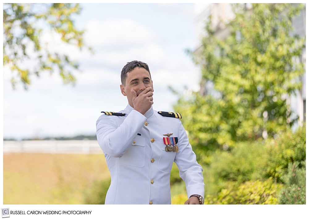 groom in dress whites, walks toward his bride, his hand to his mouth