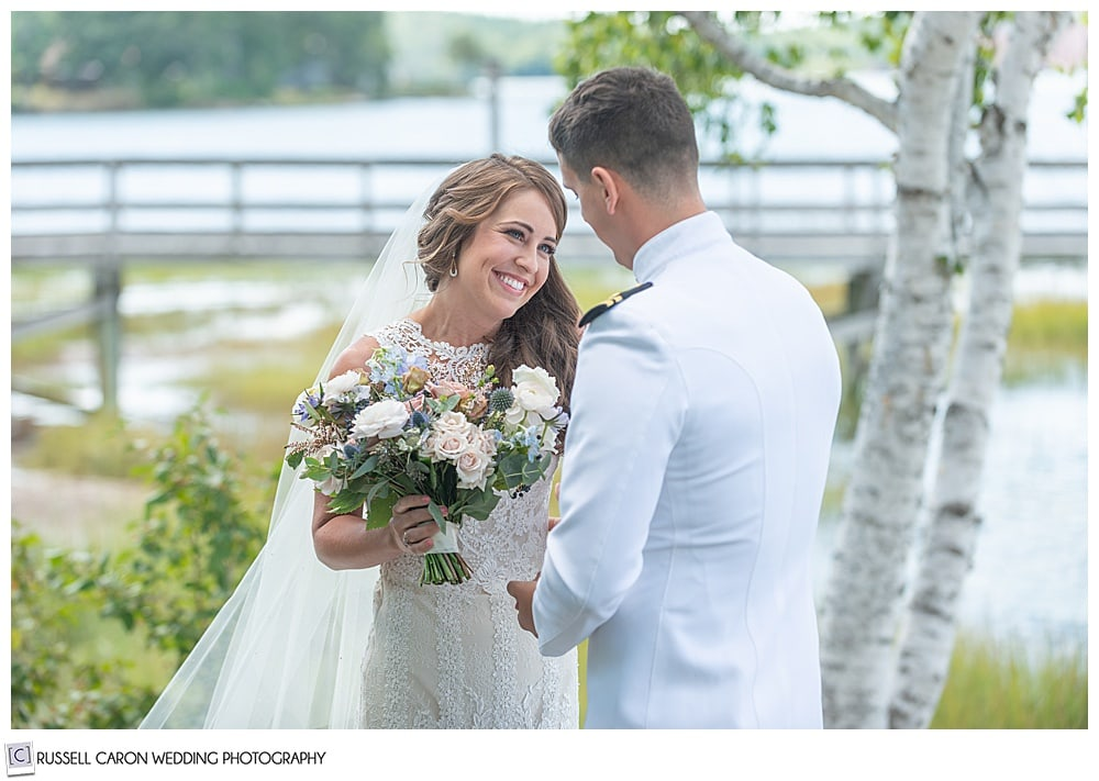 bride smiling at groom during first look photos