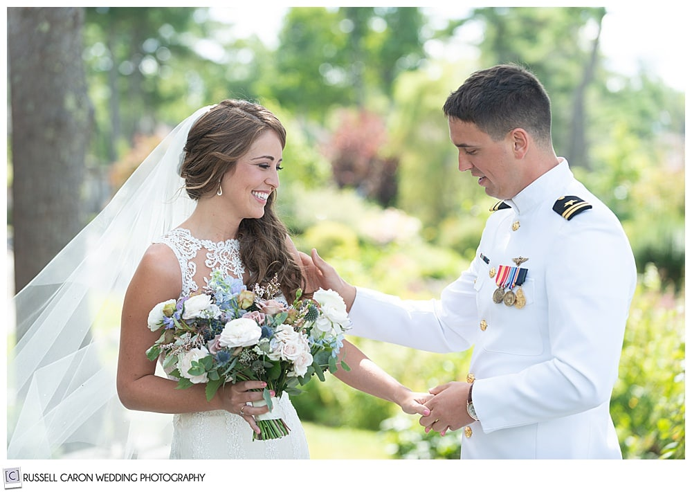 groom holding brides hand, looking at her during their first look photos