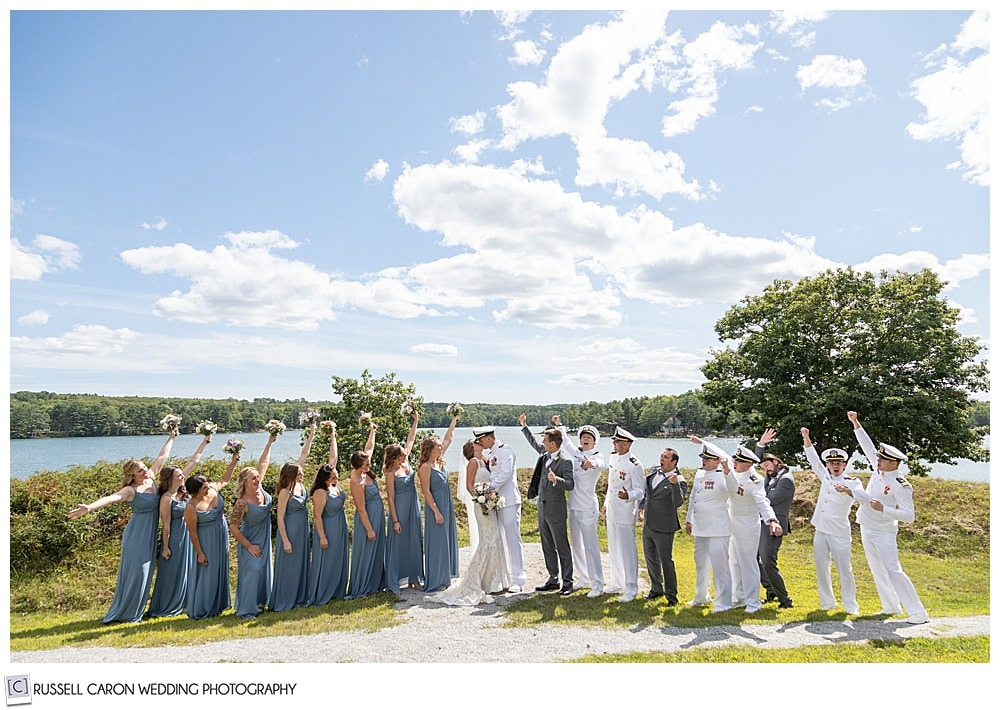 bridal party photo at Fort Edgecomb, Edgecomb, Maine. Bride and groom are kissing while the bridal party cheers