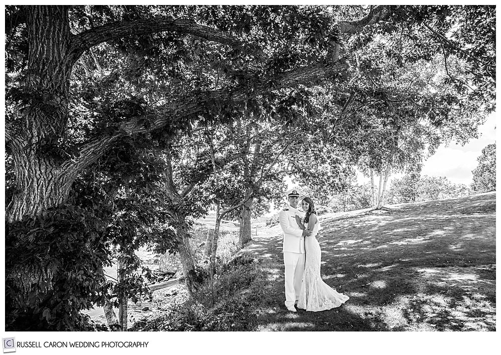 black and white photo of a bride and groom standing together looking at the camera
