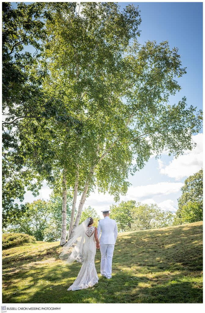 bride and groom walking away from the camera, up a hill lined with trees