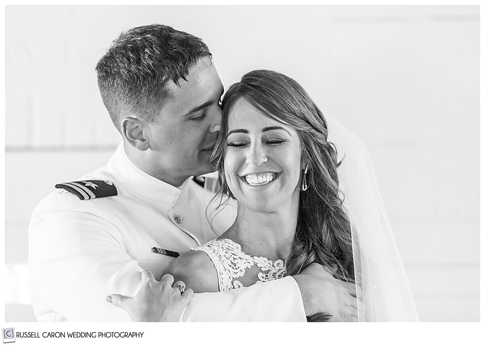black and white photo of groom whispering in bride's ear, as she smiles