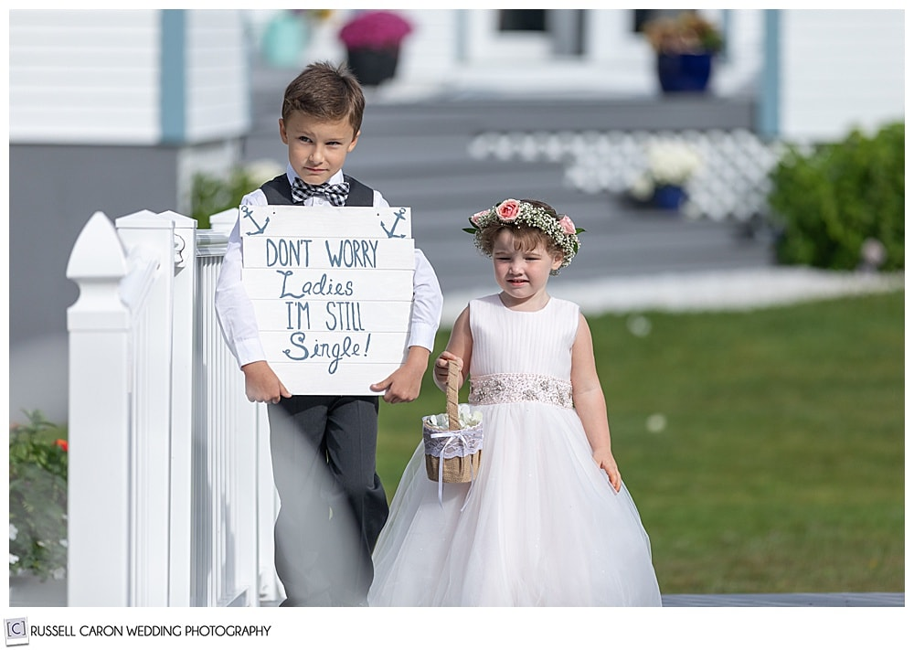 flower girl and ring bearer walking down the aisle at an outdoor wedding