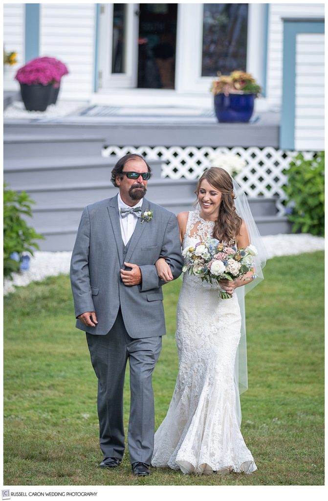 bride and her father walk towards the backyard ceremony site