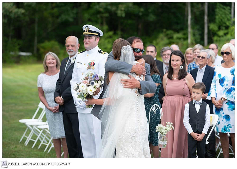 bride hugs her father after they walk down the aisle