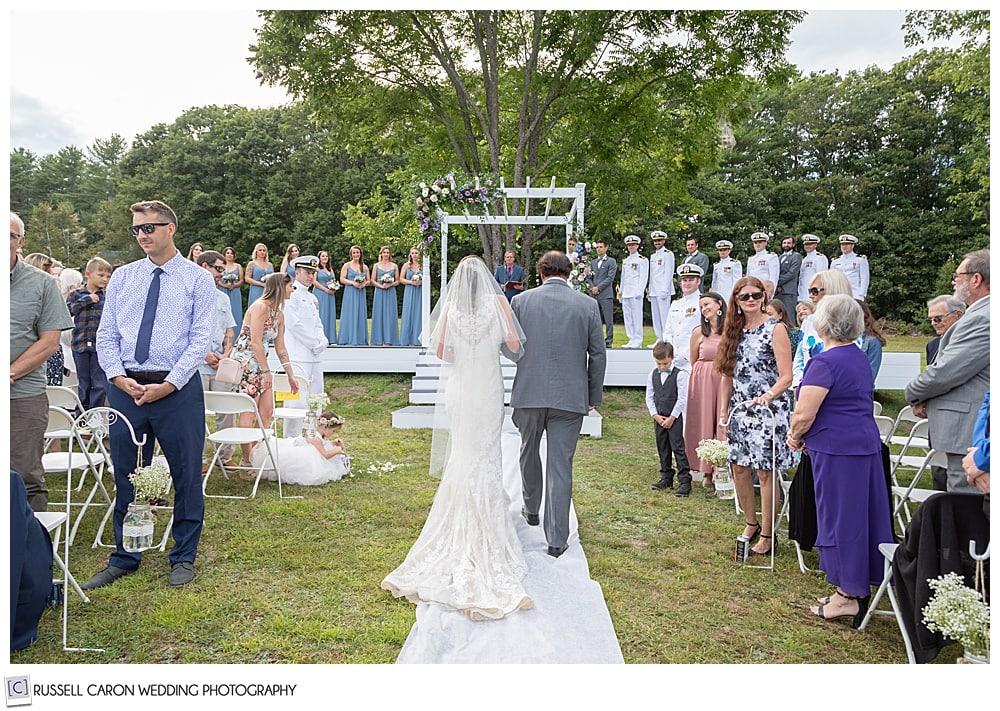 bride and her father, backs to the camera, walk toward the groom at their backyard ceremony site