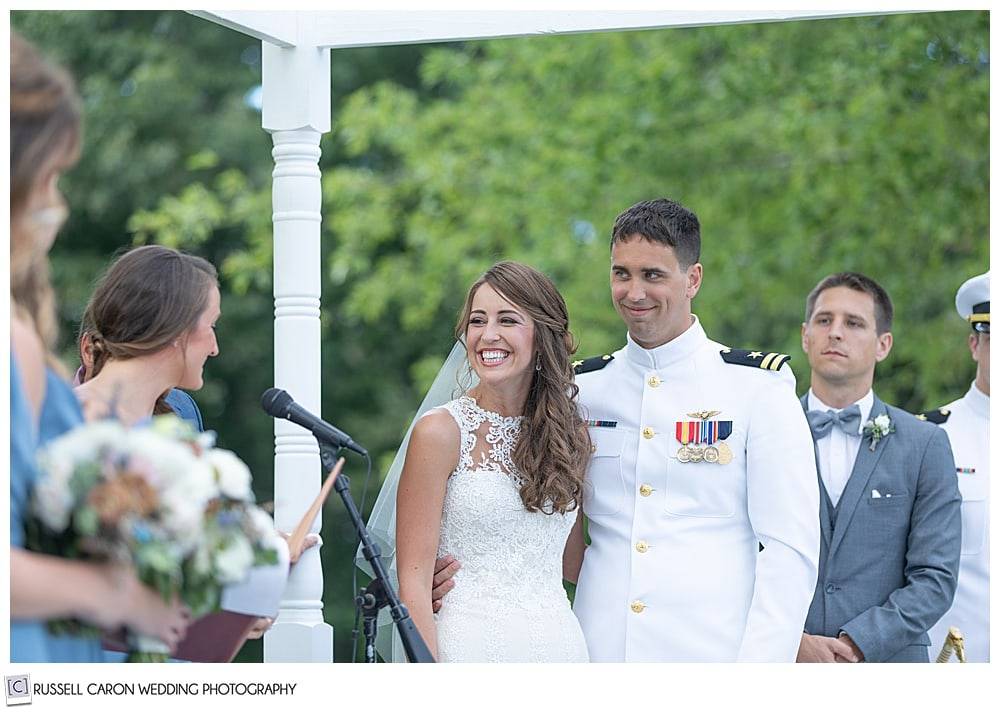 bride and groom standing side-by-side during their Dresden Maine wedding ceremony, while a bridesmaids reads