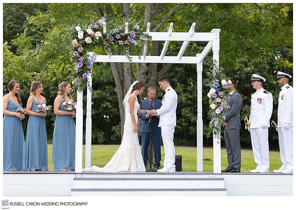 groom puts ring on the bride's finger during their backyard Dresden Maine wedding ceremony