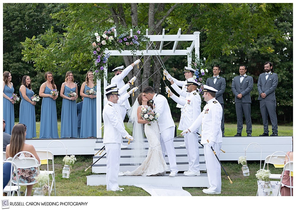 bride and groom kiss under the sword arch of groomsmen in their dress whites