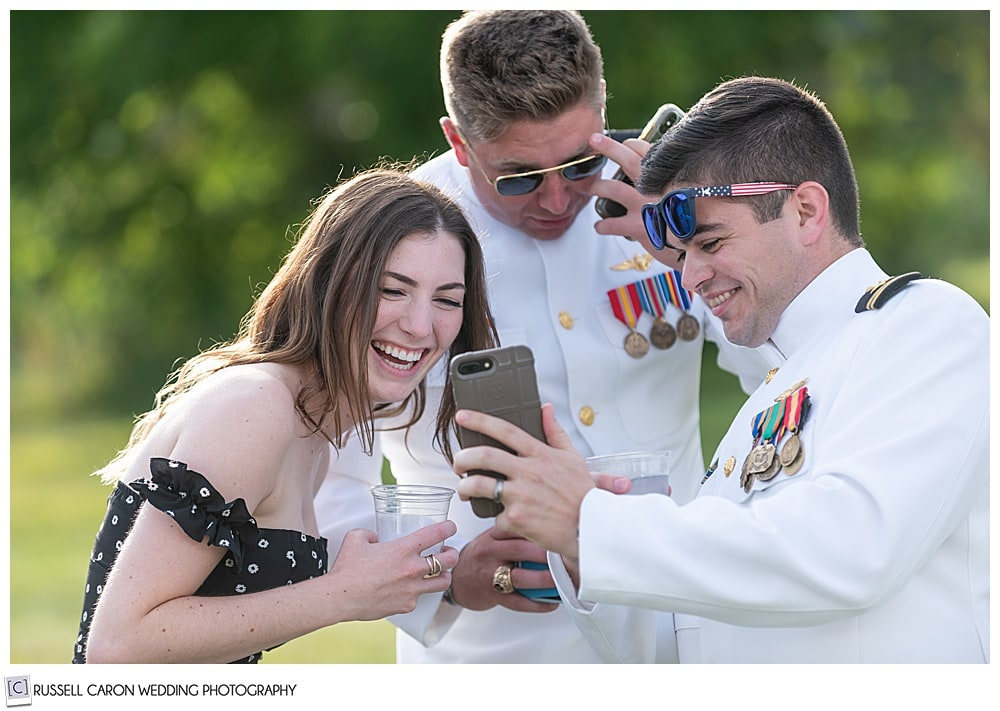 wedding guests laugh at a cell phone