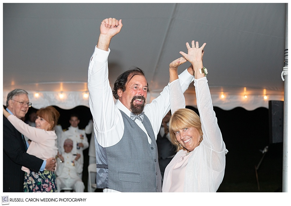 brides parents dancing, with their arms up in the air