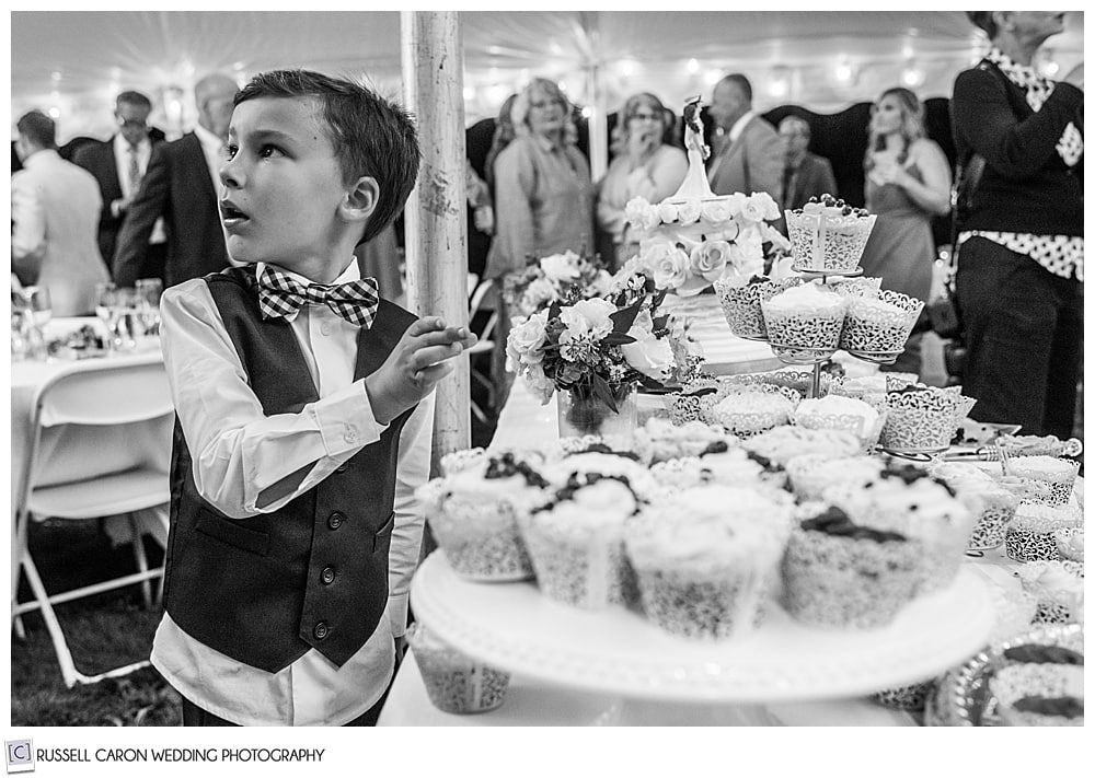 black and white photo of a boy reaching for a cupcake at a wedding, with turned head and surprised look