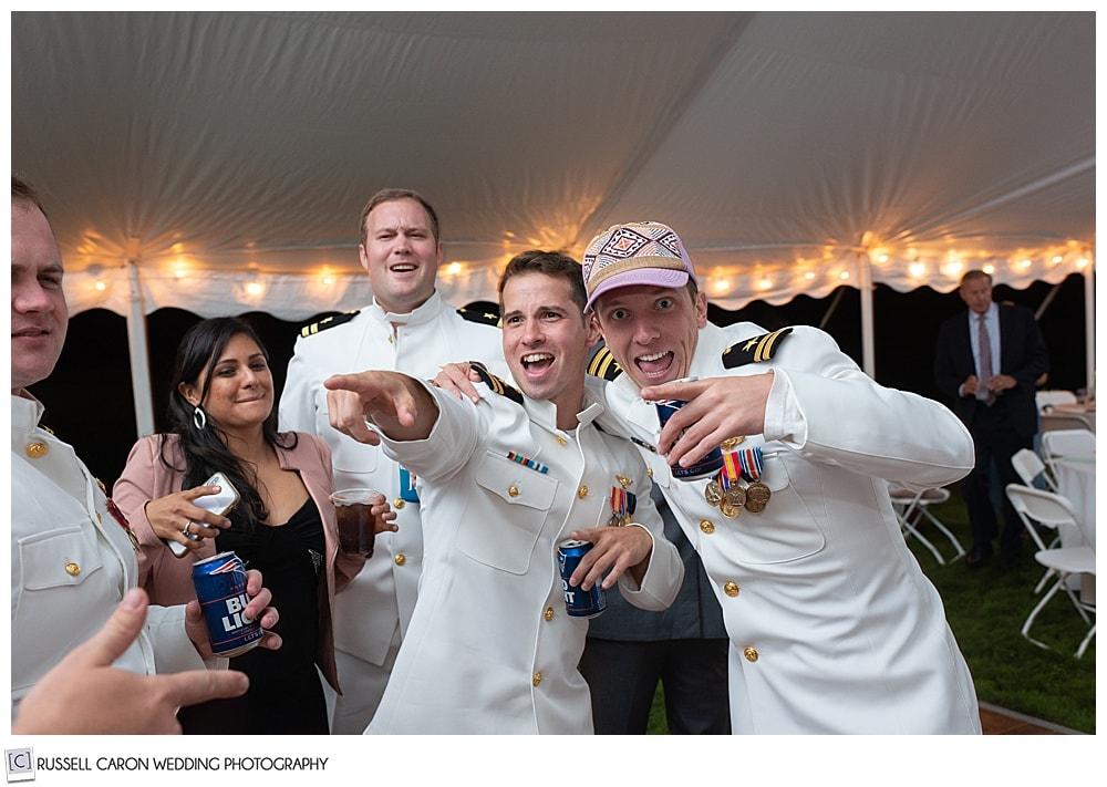 two men in dress whites having fun at a wedding reception