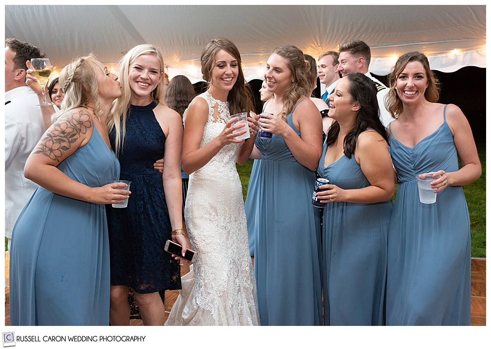 bride standing with bridesmaids and friends during her wedding reception