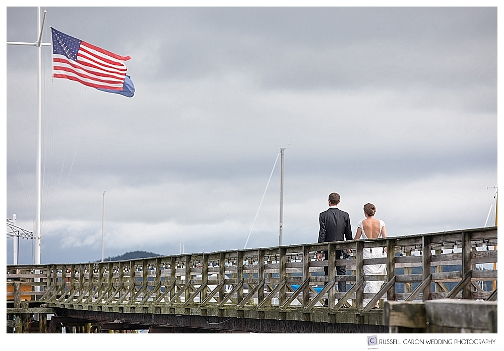 bride and groom walking on wooden dock in Castine Maine, during their elegant Castine Maine wedding
