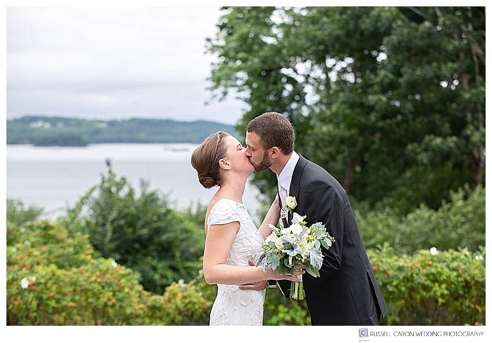 bride and groom kiss during first look at private residence elegant Castine Maine wedding