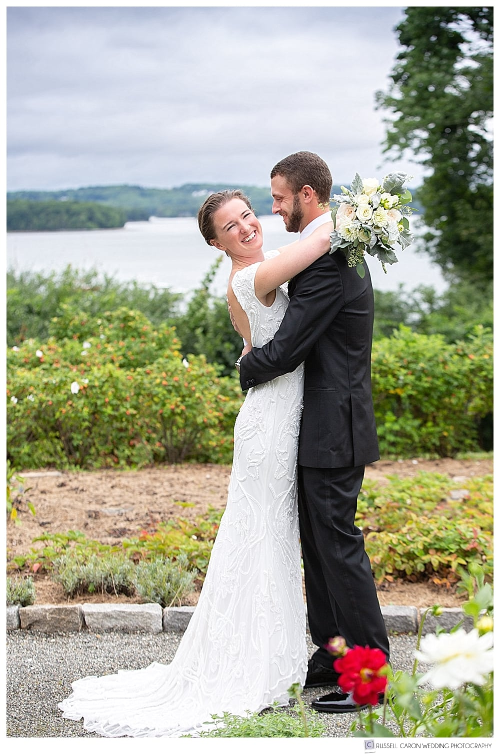 bride and groom hugging during first look photos at private residence at elegant Castine Maine wedding