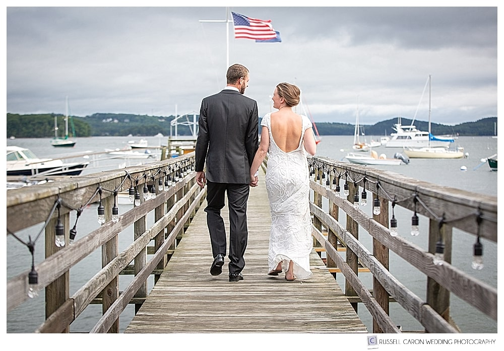 Bride and groom holding hands and walking away on a dock in Castine, Maine