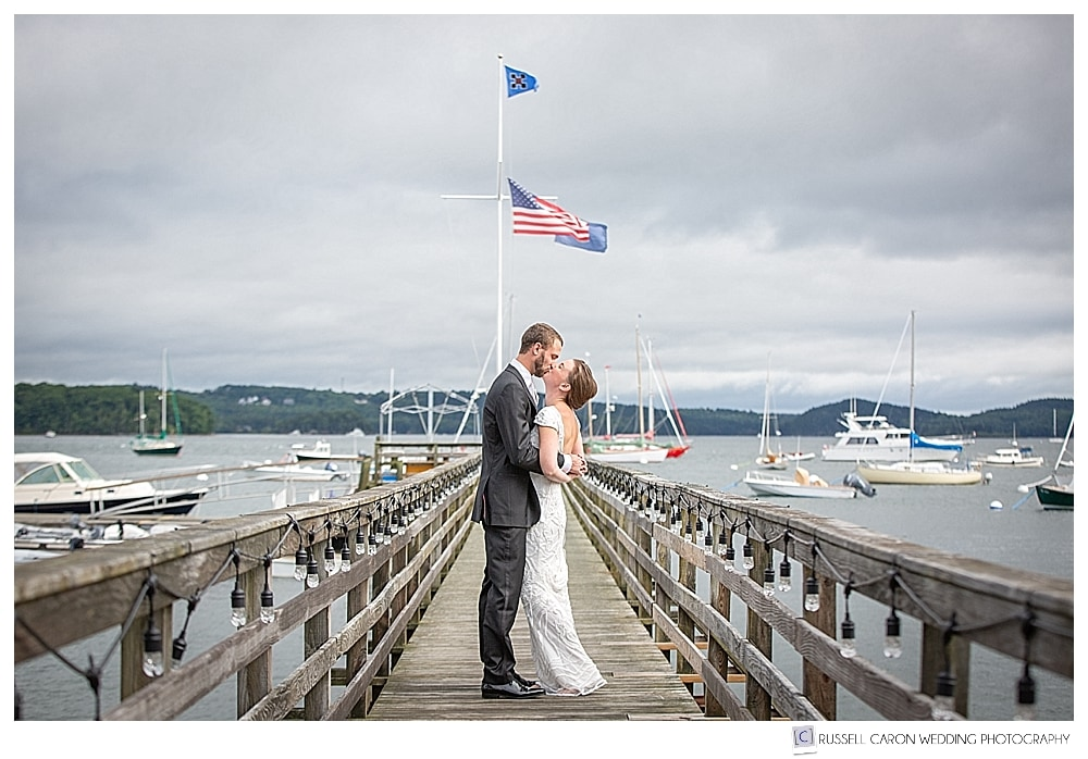 bride and groom kissing on a dock during elegant Castine, Maine wedding day