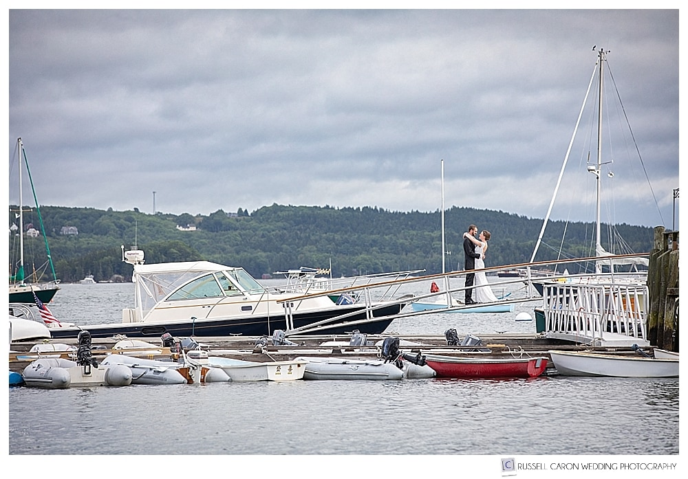 bride and groom standing together on a gangway to a dock in Castine, Maine