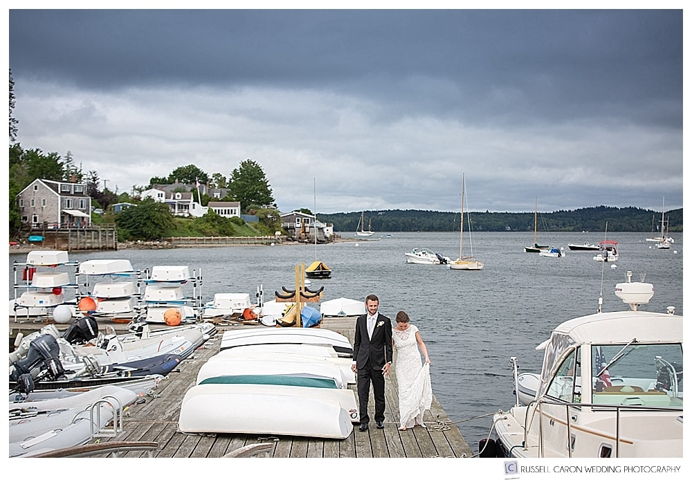 Bride and groom walk past boats on a dock in Castine, Maine