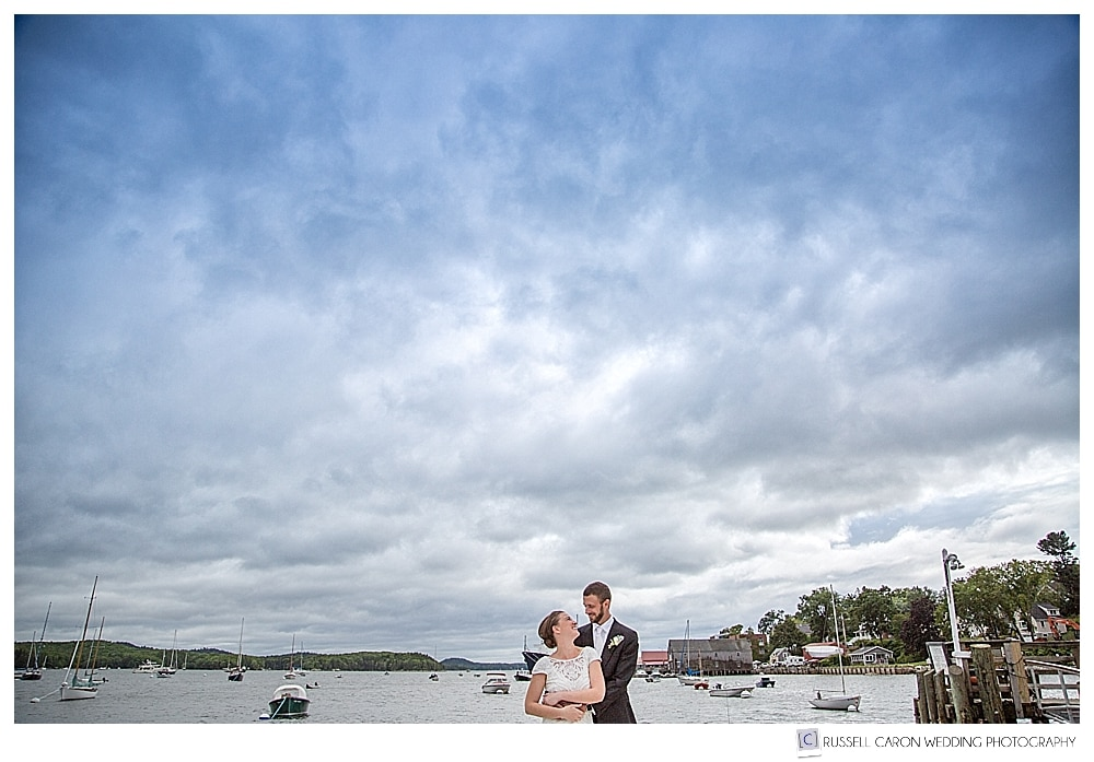 bride and groom on a dock in Castine harbor, Maine
