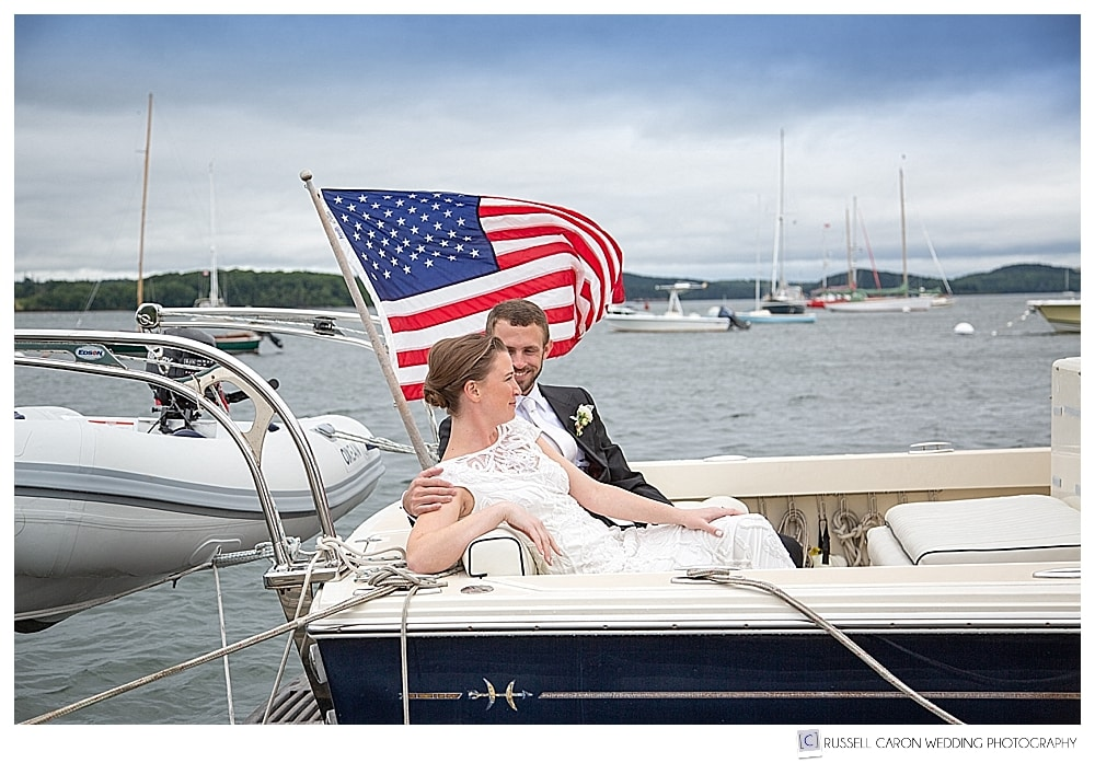 bride and groom sitting in a boat in Castine Harbor, maine